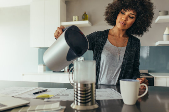 Woman making coffee at home office