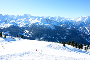 People enjoying skiing on prepared slopes in the Alps on sunny day. Beautiful snowy trees in the mountains. Perfect winter holidays destination for family in modern comfortable Alpine ski resort.