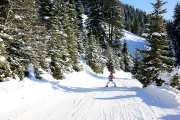 Family enjoying skiing on prepared slopes in the Alps on sunny day. Perfect winter holidays destination for children and adults in modern comfortable Alpine ski resort.