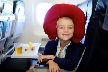 Happy little girl enjoying meal and relaxing with pillow in the airplane. Family traveling comfortable by plane to holiday destination. Children friendly airline.