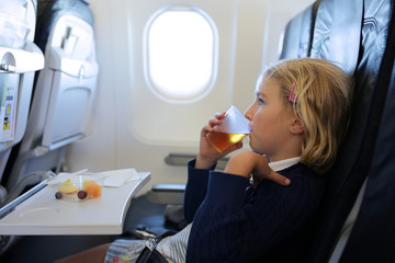 Happy little girl enjoying meal and relaxing in the airplane. Family traveling by plane to holiday destination. Children friendly airline.