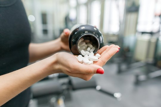 Closeup of fitness woman hands showing sports and fitness supplements, capsules, pills, gym background. Healthy lifestyle, medicine, nutritional supplements and people concept