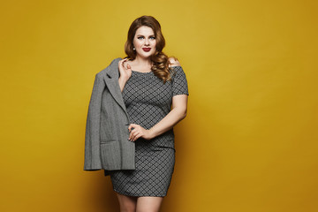 Plus size sexy model girl, fashionable blonde with bright makeup and with stylish hairstyle, in the dress with geometric patterns posing at the yellow background in a studio, isolated