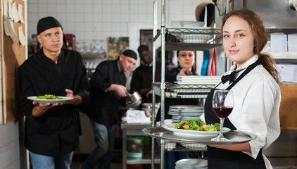 Waitress holding cooked meals at kitchen restaurant
