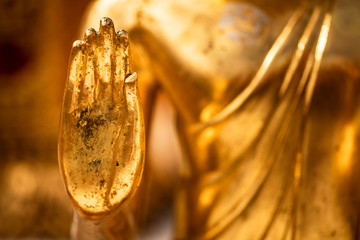 Hand of a golden Monday Buddha statue.