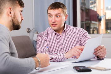 Serious man with friend discussing documents at home table