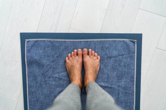 Yoga mat hot bikram yoga class - girl taking pov selfie of feet standing on towel in studio. Top view on floor.