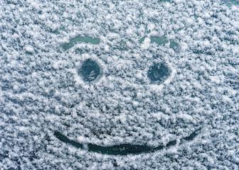 A joyful face drawn on a snowy windshield.