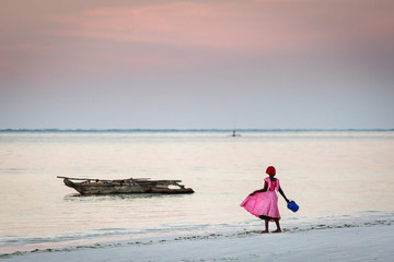 Young girl in pink playing on the beach of Zanzibar Island, Tanzania