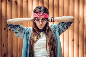 Colorful emotional portrait of young hipster woman. Crazy girl in red bandage and rock sunglasses holding her head. Hipster woman near wooden background.