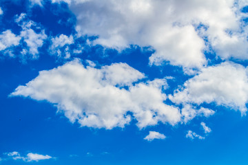 Blue summer sky with contrasting white clouds abstract background