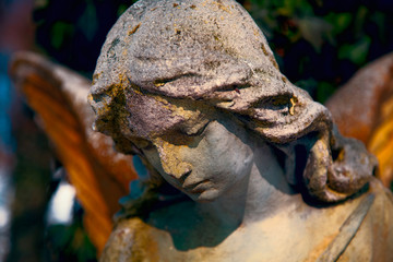 Beautiful angel stone statue with a sweet expression that looks down. Religion, faith, Christianity concept.