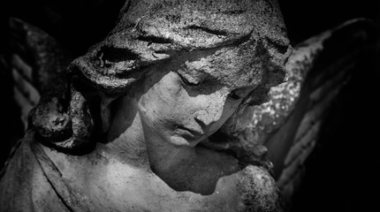 Black and white photo of antique stone statue of sad angel. Religion, faith, death, resurrection, eternity concept.