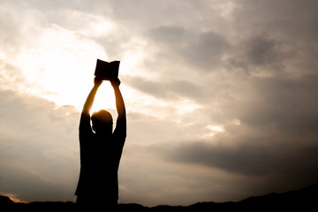 Young man lift up holy Bible to sky with light of sun background. christian concept.