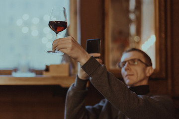 Photo with shallow depth of field, toned and stylized as a film of a man making photo with phone of glass of red wine in hand for his social media account