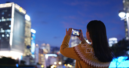 Woman take photo on cellphone in city at night