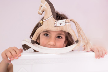 Adorable, cute little girl close-up photo of her looking thourh her wooden horse toy
