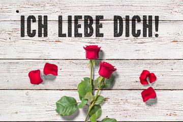 """Rose und Blütenblätter auf Holzuntergrund und Nachricht """"Ich liebe Dich!"""""""