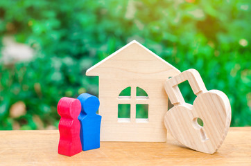 Wooden house and padlock in the shape of a heart and a couple in love on a green background. The concept of a love nest. Buying a house or apartment for a new family. trust. St. Valentine's Day