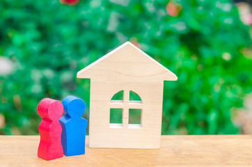 Figures of a young couple in love are standing near a wooden house. The concept of affordable and cheap housing for young families. Loans and mortgages for the purchase of their own homes.