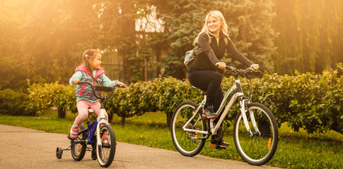 Beautiful and happy young mother teaching her daughter to ride a bicycle. Both smiling, summer park in background.