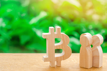 Wooden figures of people are standing near a bitcoin on a green background. Crypto currency, blockchain technology. The collapse and rise cost of bitcoin. Mining farms, miners, stock exchange crypts