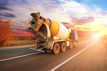 Concrete mixer truck on the countryside road against sky with sunset