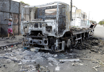 Person removes piece from burned-out truck which was transporting chickens in Fortaleza