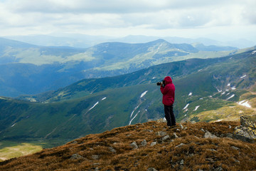 Female silhouette photographer in action. Photographing mountain landscape.Nature photography