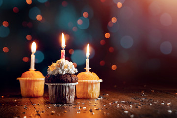 Creative background, cupcake with candles, beautiful bokeh. Happy Birthday. Present. Concept for Holiday Card, Flyer, Background. Copy space