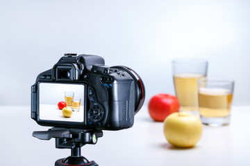 A process of taking picture of juice and apple with professional camera. Closeup