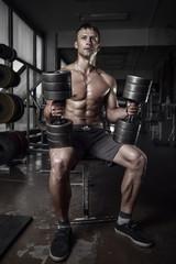 Fitness guy holding huge dumbbells