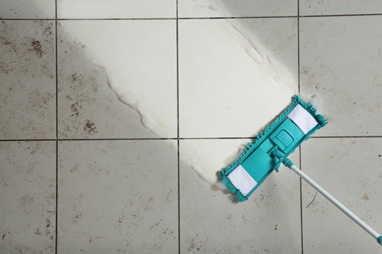 Cleaning tile floor with mop, top view. Space for text