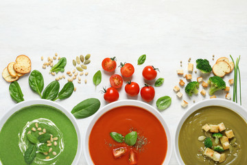 Flat lay composition with various soups and ingredients on white background. Healthy food