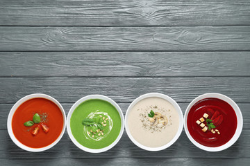 Various soups in bowls and space for text on wooden background, top view. Healthy food