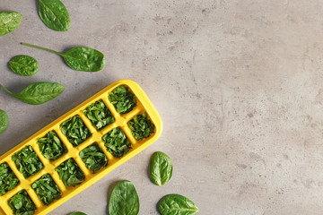 Flat lay composition with ice cube tray and spinach on grey background. Space for text