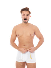 Fit man measuring his waist on white background. Weight loss