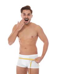 Fit man measuring his hips on white background. Weight loss