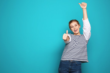 Happy young woman showing thumbs up on color background, space for text. Celebrating victory Wall mural