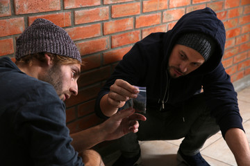 Young addicted men with hemp near brick wall