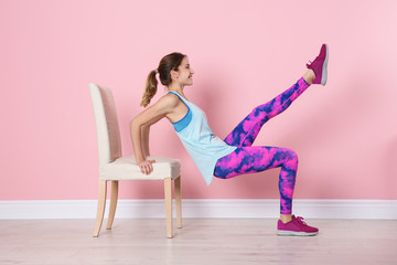 Foto auf Gartenposter Gymnastik Young woman exercising with chair near color wall. Home fitness