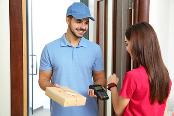 Woman with smartwatch using terminal for delivery payment indoors