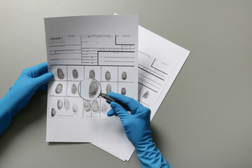Criminologist exploring fingerprints with magnifier on grey background
