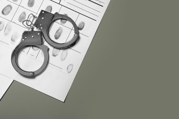 Police handcuffs and criminal fingerprints card on grey background. Space for text