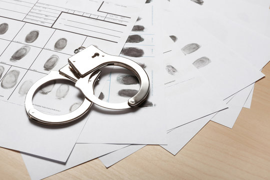 Police handcuffs and criminal fingerprints card on wooden background, space for text