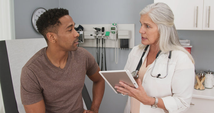 Portrait of young black man consulting with mature female doctor indoors medical clinic. Close up of senior caucasian doctor using tablet computer to share test results with male black patient