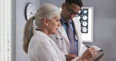 Senior female doctor taking notes of patients ct scan while consulting with young colleague. Elderly medical physician writing on clipboard and talking to young assistant