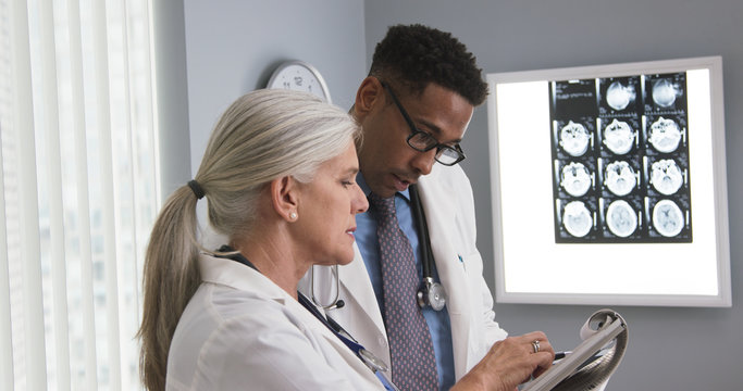 Senior medical doctor consulting with colleague on patients health condition. Two doctors reviewing medical record of patient with head injury