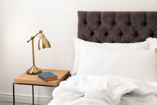 Comfortable bed and nightstand in modern room interior