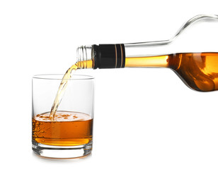 Pouring expensive whiskey into glass on white background